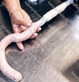 Начните подавать для домашней колбасы фарш из машинки, медленно и равномерно.