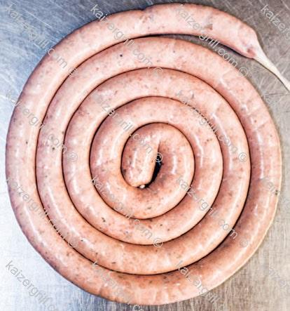 Как только вы закончили набивку домашней колбасы, сверните колбасу в спираль.